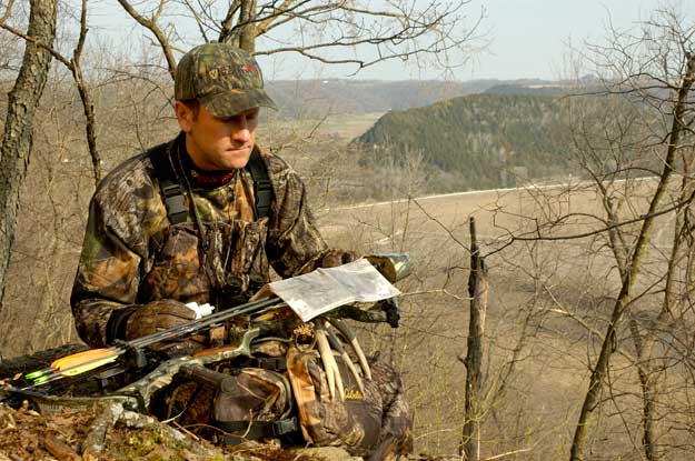 hunter reading a map on a ridgetop