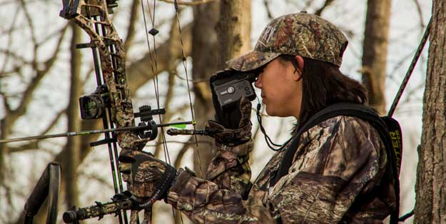 female hunter in tree stand with bow